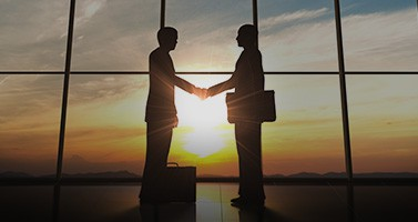 Silhouette of Two Business Men Shaking Hands Against Sunset